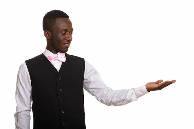 Młody szczęśliwy afrykański kelner, uśmiechając się i pokazując coś