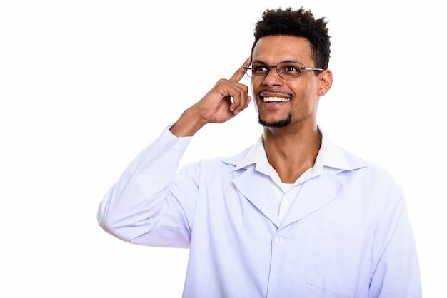 Młody szczęśliwy afrykański mężczyzna lekarz uśmiecha się myśląc palcem na głowie