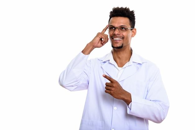 Młody szczęśliwy afrykański mężczyzna lekarz uśmiecha się podczas myślenia i wskazuje palcem w górę