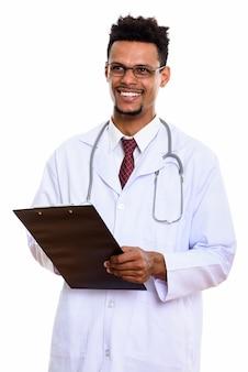 Młody szczęśliwy afrykański mężczyzna lekarz uśmiecha się trzymając schowek i myślenia