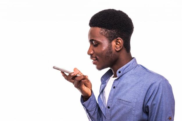 Młody szczęśliwy afrykański mężczyzna opowiada telefon komórkowego odizolowywającego na biel ścianie