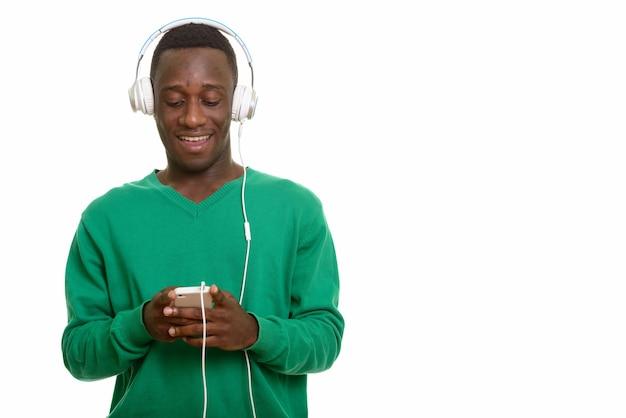 Młody szczęśliwy afrykański mężczyzna uśmiecha się i używa telefonu komórkowego