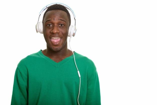 Młody szczęśliwy afrykański mężczyzna uśmiecha się podczas słuchania muzyki w słuchawkach