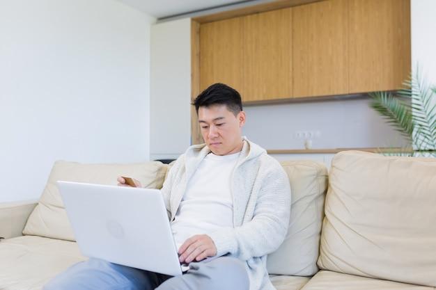 Młody szczęśliwy azjata robi zakupy online w sklepie internetowym za pomocą laptopa i karty kredytowej