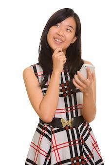 Młody szczęśliwy azjatycki bizneswoman trzyma telefon komórkowy podczas myślenia
