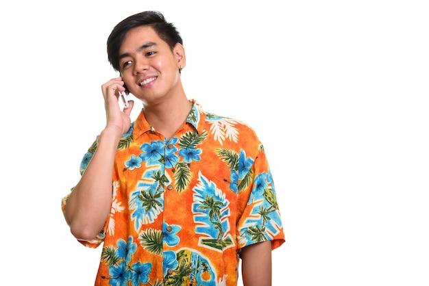Młody szczęśliwy azjatycki mężczyzna uśmiecha się i mówi na telefonie komórkowym
