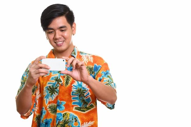 Młody szczęśliwy azjatycki mężczyzna uśmiecha się i robi zdjęcie z telefonu komórkowego pho