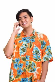 Młody szczęśliwy azjatycki mężczyzna uśmiecha się i rozmawia przez telefon komórkowy podczas