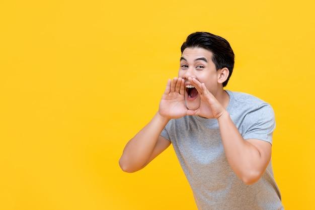 Młody szczęśliwy azjatykci mężczyzna krzyczy z ręki filiżanką wokoło usta