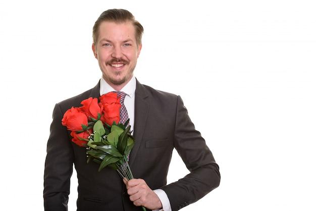 Młody szczęśliwy biznesmen posiadający czerwone róże gotowe na walentynki