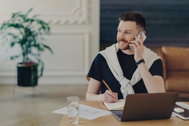 Młody szczęśliwy biznesmen pracujący w domu, mężczyzna freelancer w stroju casual rozmawia przez telefon w swoim miejscu pracy i uśmiechnięty, mając laptopa i szklankę wody na biurku. koncepcja pracy zdalnej