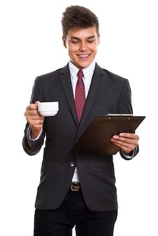 Młody szczęśliwy biznesmen uśmiecha się podczas czytania w schowku i trzymając filiżankę kawy