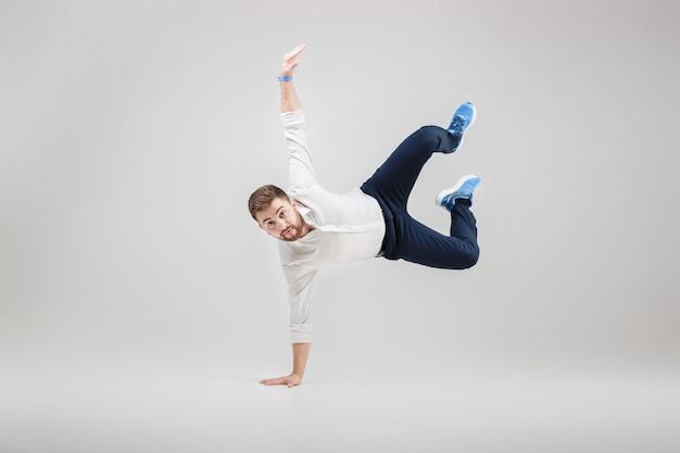 Młody szczęśliwy biznesmen z brodą w koszulowej przerwie tanczy na gre