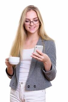 Młody szczęśliwy bizneswoman uśmiecha się podczas korzystania z telefonu komórkowego