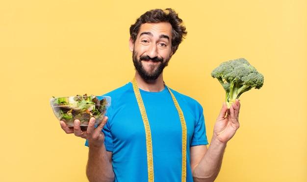 Młody szczęśliwy brodaty mężczyzna trzyma warzywa