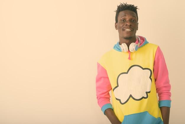 Młody szczęśliwy czarny afrykański mężczyzna uśmiecha się podczas noszenia słuchawek na szyi