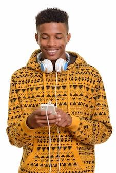 Młody szczęśliwy człowiek afryki przy użyciu telefonu komórkowego podczas noszenia headpho