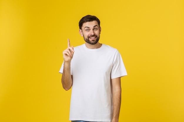 Młody szczęśliwy człowiek dostaje dobry pomysł, podnosi palec do przodu, gdy chce to wypowiedzieć, ciesząc się, że ma na myśli genialne myśli, na białym tle nad