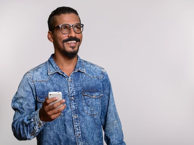 Młody szczęśliwy człowiek indyjski trzymając telefon komórkowy podczas myślenia na szarym tle