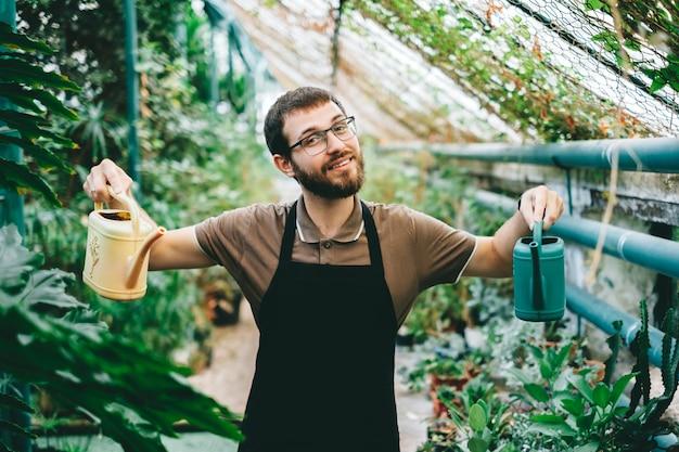 Młody szczęśliwy człowiek ogrodnik ekolog, trzymając konewki w rękach, dbający o rośliny w szklarni.