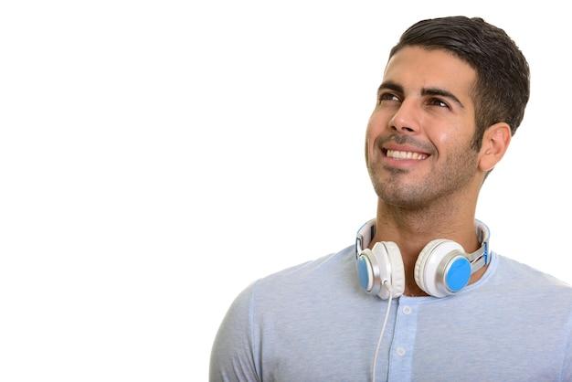 Młody szczęśliwy człowiek perski uśmiecha się i myśli podczas noszenia słuchawek