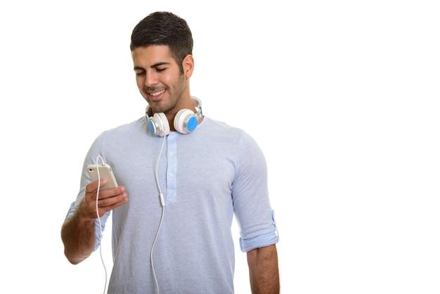 Młody szczęśliwy człowiek perski uśmiecha się i używa telefonu komórkowego podczas noszenia słuchawek