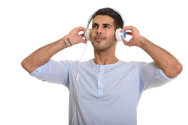 Młody szczęśliwy człowiek perski uśmiechnięty podczas słuchania muzyki