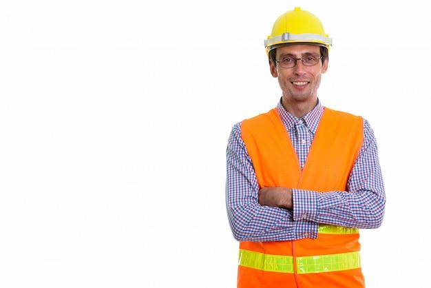 Młody szczęśliwy człowiek pracownik budowlany uśmiechnięty podczas noszenia okularów z rękami skrzyżowanymi