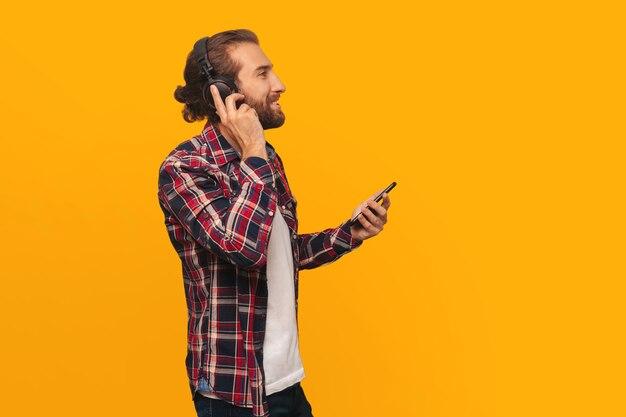 Młody, szczęśliwy człowiek słucha muzyki na słuchawkach, trzyma w rękach smartfon, odwraca wzrok i uśmiecha się, na żółtym tle