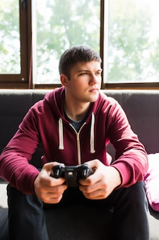 Młody szczęśliwy człowiek śmiejąc się i grając w gry wideo w weekend
