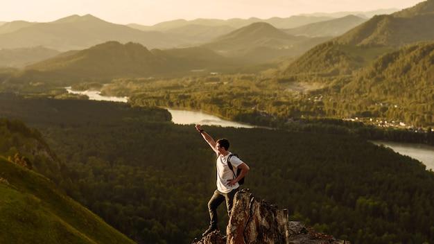 Młody szczęśliwy człowiek turysta z uśmiechem na twarzy podnosi rękę jako zwycięzca na tle górskiej doliny i rzeki o zachodzie słońca. koncepcja podróży do przyrody i gór