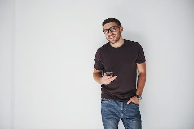 Młody szczęśliwy człowiek ubrany na co dzień inteligentny telefon na białym tle