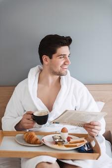Młody szczęśliwy człowiek ubrany w biały szlafrok, mając śniadanie i czytając gazetę, siedząc na łóżku w apartamencie hotelowym