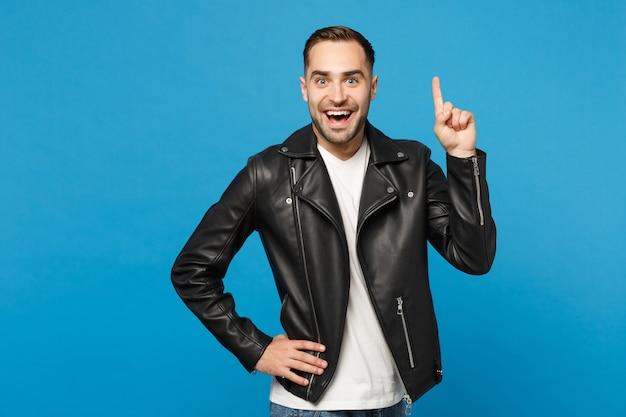 Młody szczęśliwy człowiek w czarnej kurtce biały t-shirt patrząc aparat, trzymając palec wskazujący się z świetnym nowym pomysłem na białym tle na tle niebieskiej ściany portret studio. koncepcja życia ludzi. makieta miejsca na kopię