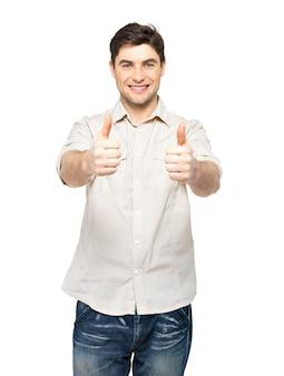 Młody szczęśliwy człowiek z aprobatami podpisuje przypadkowe na białym tle na białej ścianie.