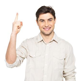 Młody szczęśliwy człowiek z dobrym pomysłem podpisuje dorywczo na białym tle na białej ścianie.