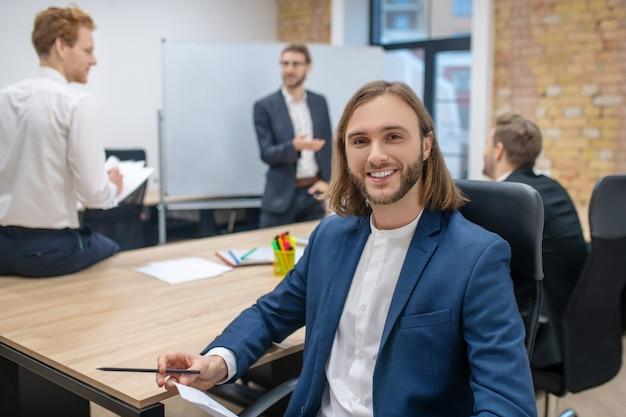 Młody szczęśliwy człowiek z papierami i ołówkiem siedzi przy stole i rozmawia kolegów z tyłu w biurze