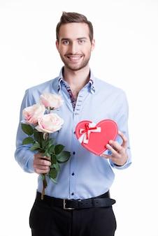 Młody szczęśliwy człowiek z różowymi różami i prezentem - na białym tle
