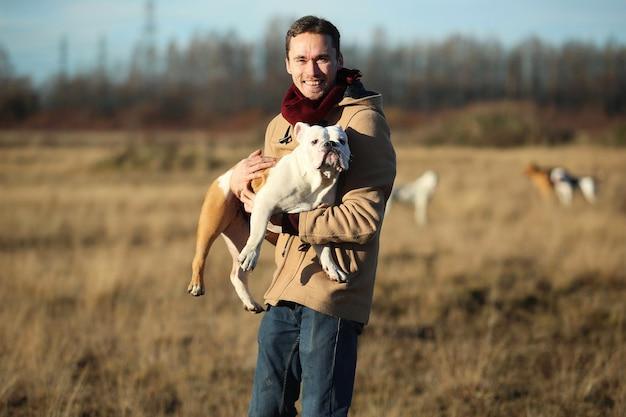 Młody szczęśliwy europejski uśmiechnięty i śmiejąc się trzymając w rękach psa buldog angielski