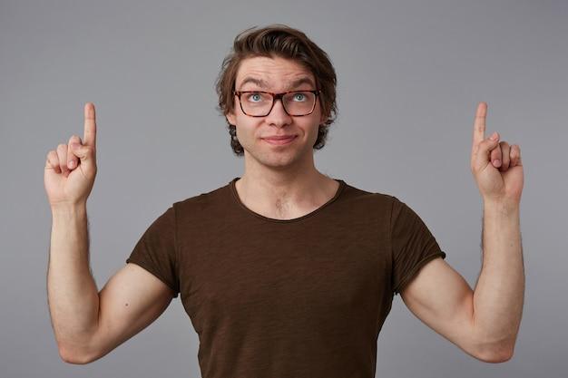 Młody szczęśliwy facet w okularach, stoi na szarym tle z zaskoczonym wyrazem twarzy, wskazuje palcami w górę nad głową, patrzy w górę i uśmiecha się.