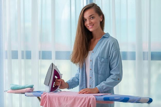 Młody szczęśliwy gospodyni domowej prasowanie po pralni na prasowanie desce