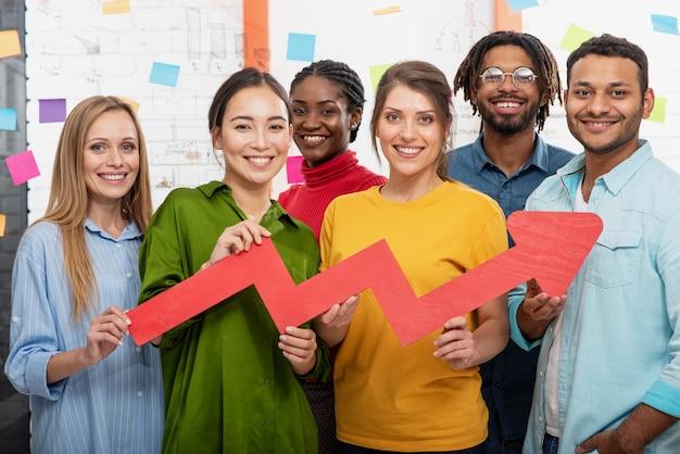 Młody szczęśliwy i kolorowy zespół biznesowy w biurze trzyma czerwoną strzałkę statystyczną