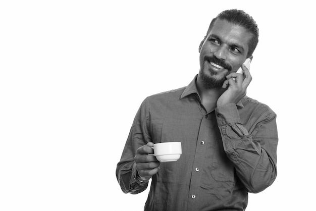 Młody szczęśliwy indyjski biznesmen rozmawia przez telefon komórkowy i trzymając filiżankę kawy podczas myślenia