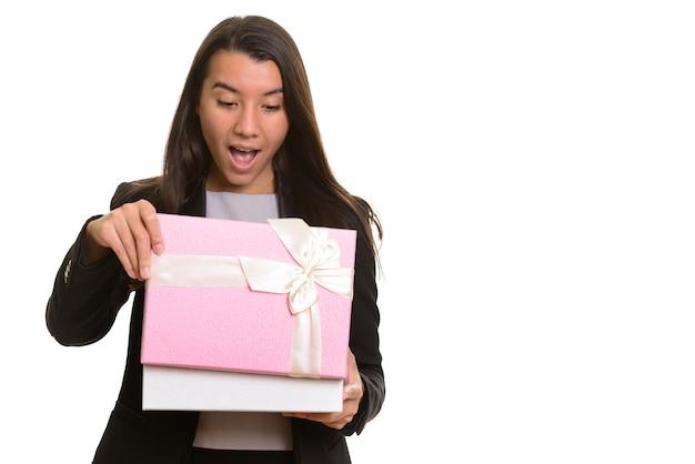 Młody szczęśliwy kaukaski bizneswoman uśmiecha się i otwiera pudełko na białym tle