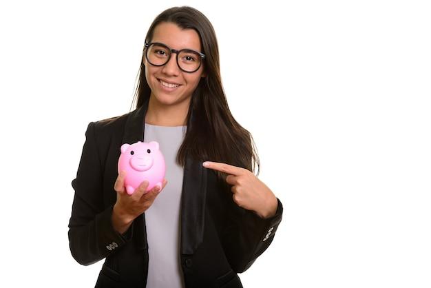Młody szczęśliwy kaukaski bizneswoman uśmiecha się skarbonkę i trzyma wskazując palcem