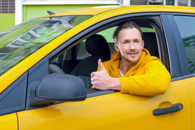 Młody szczęśliwy kierowca taksówki mężczyzna siedzi za kierownicą taksówki i pokazuje jak