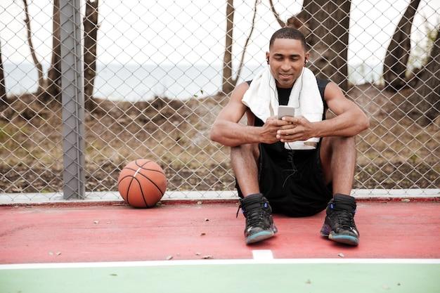 Młody szczęśliwy koszykarz siedzi w parku z ręcznikiem w pobliżu koszykówki i rozmawia podczas słuchania muzyki