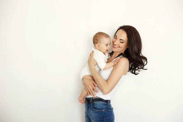 Młody szczęśliwy macierzysty uśmiechnięty mienie patrzeje jej dziecko córki nad biel ścianą.