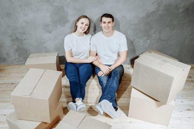 Młody szczęśliwy małżeństwo mężczyzna i kobieta siedzą na podłodze wśród ruchomych pudeł w ich nowym domu.