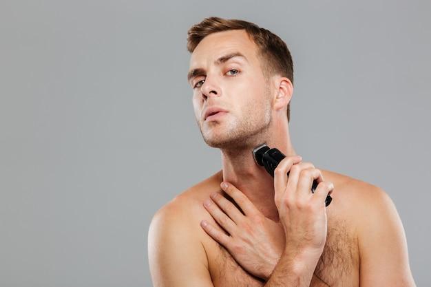 Młody szczęśliwy mężczyzna golący się elektryczną maszynką do golenia odizolowaną na szarej ścianie